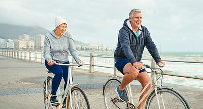 Buy stock photo Shot of a mature couple riding their bicycles along the boardwalk together