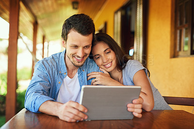 Buy stock photo Shot of a young couple using a digital tablet together outdoors