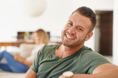 Buy stock photo Shot of a happy young man relaxing at home with his girlfriend in the background