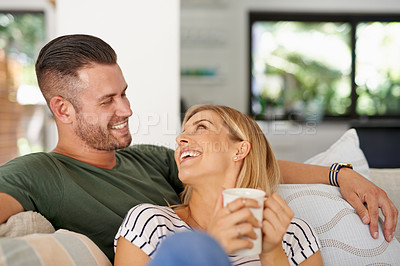 Buy stock photo Cropped shot of a young married couple being affectionate while chilling on the sofa at home