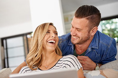 Buy stock photo Cropped shot of a young married couple using a tablet in the living room at home