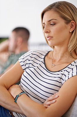 Buy stock photo Shot of a unhappy couple sitting apart from each other on a sofa after a argument at home