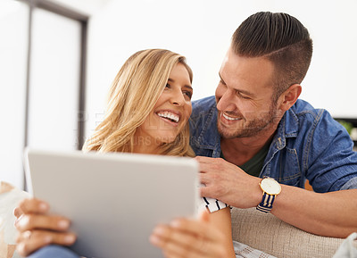 Buy stock photo Cropped shot of a young married couple using a tablet together in the living room at home