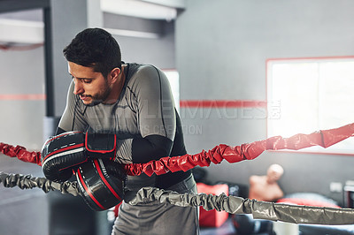 Buy stock photo Cropped shot of a professional fighter training in the gym