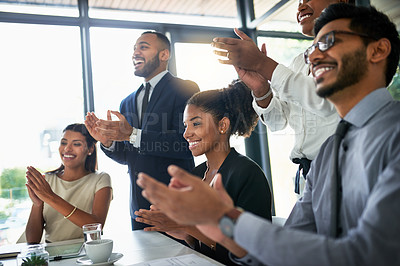 Buy stock photo Shot of a team of businesspeople clapping hands in the boardroom