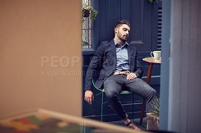 Buy stock photo Cropped shot of a young handsome businessman exhausted, resting at a cafe