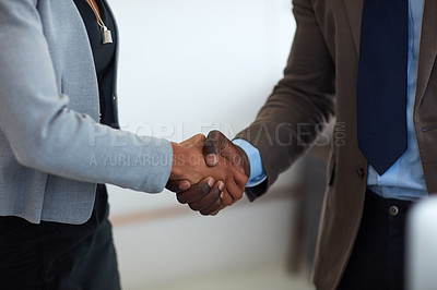 Buy stock photo Cropped shot of an unrecognizable businessman and businesswoman shaking hands in the office