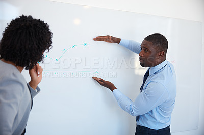 Buy stock photo Cropped shot of a young businessman explaining information on a whiteboard to his female colleague in the office