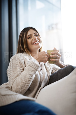 Buy stock photo Cropped shot of a young woman enjoying a cup of coffee while relaxing at home