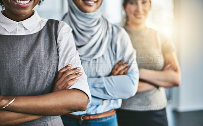 Buy stock photo Shot of a group of confident young businesswomen standing with their arms folded inside of the office at work