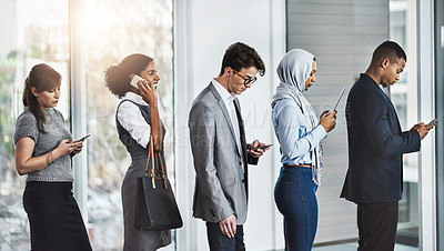 Buy stock photo Shot of a group of businesspeople standing in a row while texting on their phones in the office at work during the day