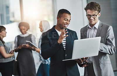Buy stock photo Shot of a group of young cheerful businesspeople browsing on digital devices while working together in the office at work