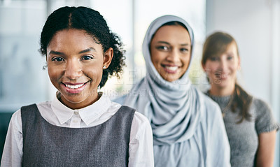 Buy stock photo Portrait of a group of young confident businesswomen standing in a row behind each other inside of the office during the day
