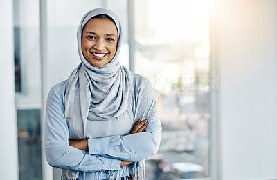 Buy stock photo Portrait of a confident young businesswoman standing with her arms folded inside the office at work