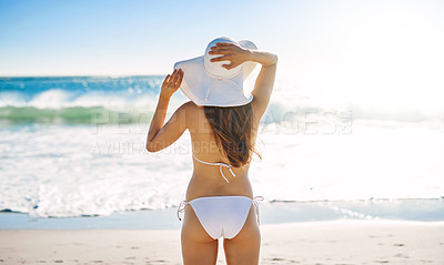 Buy stock photo Rearview shot of a young woman admiring the view while sitting on the beach