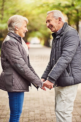 Buy stock photo Cropped shot of an affectionate senior couple out for a walk in the park
