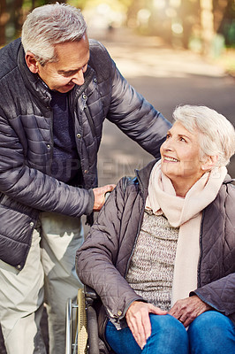 Buy stock photo Cropped shot of a wheelchair-bound senior woman spending the day with her husband in the park