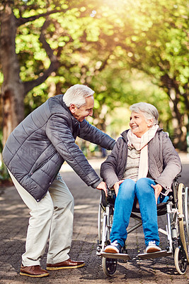 Buy stock photo Full length shot of a wheelchair-bound senior woman spending the day with her husband in the park