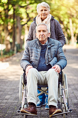 Buy stock photo Full length shot of a wheelchair-bound senior man spending the day with his wife in the park