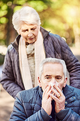 Buy stock photo Cropped shot of a wheelchair-bound senior man and his wife blowing their noses while out at the park