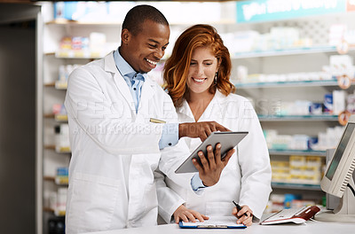 Buy stock photo Shot of two pharmacists working together on a digital tablet in a chemist