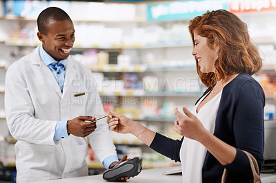 Buy stock photo Shot of a customer using a credit card to pay for a purchase in a pharmacy
