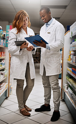 Buy stock photo Shot of two pharmacists working together in a chemist