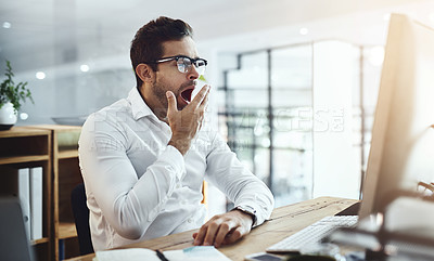 Buy stock photo Shot of a young businessman yawning while working in an office