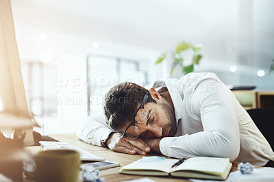 Buy stock photo Shot of a young businessman sleeping at his desk in an office