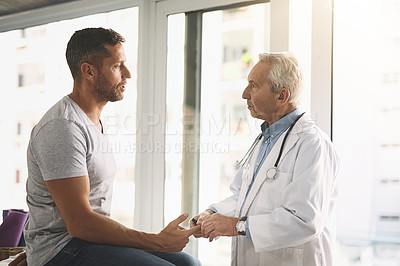 Buy stock photo Cropped shot of a senior doctor giving his male patient a thorough checkup during his consultation