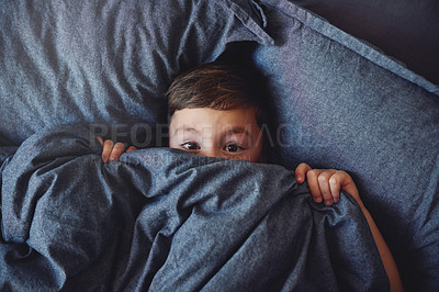 Buy stock photo Portrait of an adorable little boy lying in bed while peeking from underneath a blanket at home