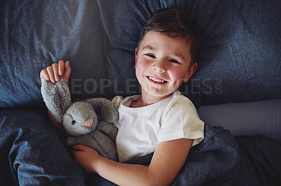 Buy stock photo Portrait of an adorable little boy lying in bed at home
