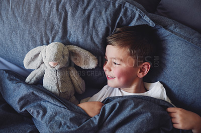 Buy stock photo High angle shot of an adorable little boy lying in bed at home