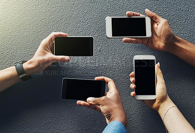 Buy stock photo Shot of unrecognizable people holding smartphones against a grey background