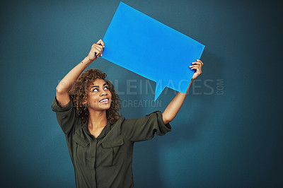 Buy stock photo Studio shot of a woman holding a speech bubble against a blue background