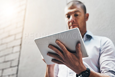 Buy stock photo Low angle shot of a handsome young man using his tablet outside