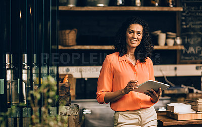 Buy stock photo Portrait of a mature woman using a digital tablet while working in a coffee shop