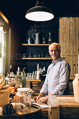Buy stock photo Portrait of a mature man going over paperwork while working in a coffee shop
