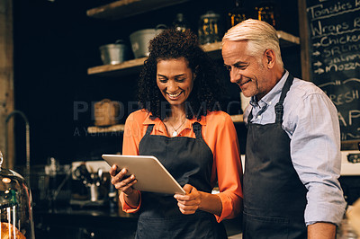 Buy stock photo Shot of a mature man and woman using a digital tablet while working in a coffee shop