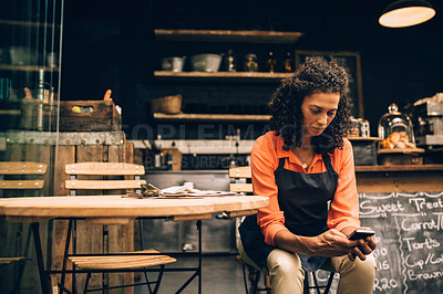 Buy stock photo Shot of a mature woman using a mobile phone while working in a coffee shop