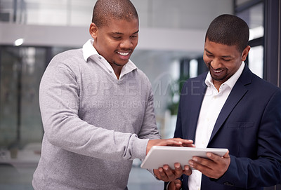 Buy stock photo Shot of two young businessmen using a digital tablet together in a modern office