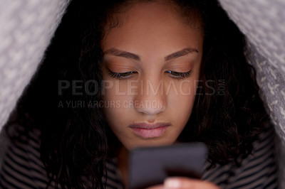 Buy stock photo Cropped shot of a teenage girl using a cellphone laying underneath a blanket in her bedroom at home