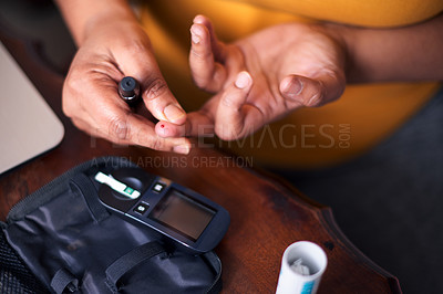 Buy stock photo Cropped shot of a mature woman using a blood sugar test on her finger