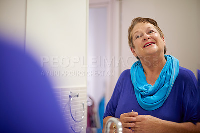 Buy stock photo Shot of happy senior woman admiring herself in the bathroom mirror