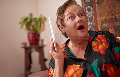 Buy stock photo Shot of a senior woman using a digital tablet and looking surprised