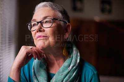 Buy stock photo Shot of a senior woman looking thoughtfully out of a window at home