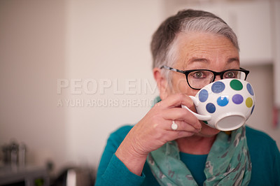 Buy stock photo Shot of a senior woman drinking a warm beverage at home