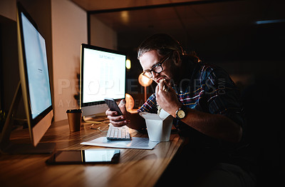 Buy stock photo Shot of a young businessman working late at night in a modern office