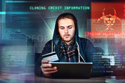 Buy stock photo Cropped shot of a young male hacker committing credit card fraud late at night in the office