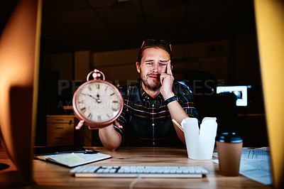 Buy stock photo Cropped shot of a young businessman holding a clock worrying about his deadline while working late in the office
